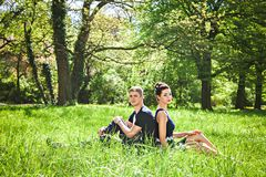 Man and woman sitting at grass in park Royalty Free Stock Photos