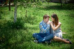 Man and woman sitting on the grass. Man and women sitting on the grass in the spring garden Royalty Free Stock Photography