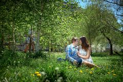 Man and woman sitting on the grass. Man and women sitting on the grass in the spring garden Stock Photo