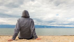 Man or woman is sitting in a hoodie on the beach. Back view. Time lapse 4K stock footage