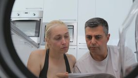 A man and a woman sitting in the house in front of a non-working washing machine studying the user manual. stock video footage