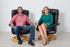 Man and woman sitting on leather chairs in the studio Stock Images