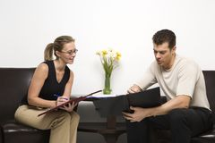 Man and woman sitting looking at portfolios. Stock Photo