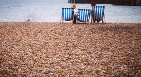 Man and Woman Sitting on Lounge Chair While on Seashore during Daytime Stock Photography