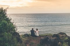 Man and Woman Sitting Near Body of Water Royalty Free Stock Image
