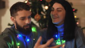 Man and woman sitting near christmas tree with a garland around the neck close up. Lovers talking and smiling. Happy. Bearded man and pretty woman sitting near stock video footage