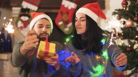 Man and woman sitting near christmas year tree, waving sparklers in hands. Woman gives present to man, they kissing. Man and woman in home clothes sitting near stock video footage