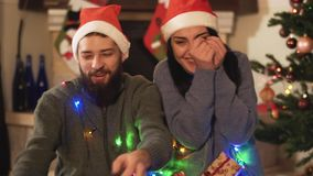 A man and a woman are sitting near the New Year tree and catching gifts that are thrown at them. Happy couple have. A man and a woman are sitting near the New stock video footage
