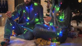 Man and woman sitting near new year tree with a garland around the neck close up. People waving garlands and serpentine. Man and woman sitting near new year tree stock video