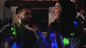 Man and woman sitting at christmas tree with a garland. The girl scratching beard of the man, both lovers smiling. Happy. Man and woman sitting near new year stock video
