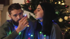 Man and woman sitting near new year tree with a garland around the neck. Girl caress hair of her boyfriend, beardie kiss. Her cheek. Happy adult couple have stock footage