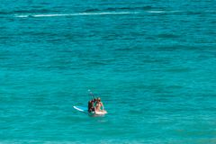 Man and woman sitting in a paddle board surrounded by water at t royalty free stock photo
