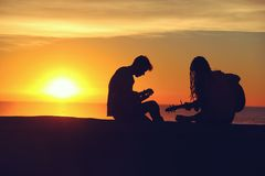 Man and Woman Sitting and Playing Guitar Stock Photo