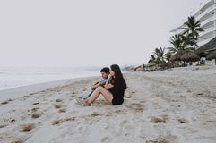 Man And Woman Sitting On Sand Stock Photography