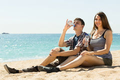 Man and woman sitting on the sand and drink  water Royalty Free Stock Photography