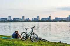 Man and woman sitting on the shore and look at the city Royalty Free Stock Photography
