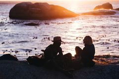 Man and Woman Sitting on Shore Near Body of Water during Sunset royalty free stock images
