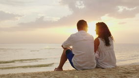 A man and a woman are sitting side by side on the sand on the beach. Together they look at the sunset over the sea stock video footage