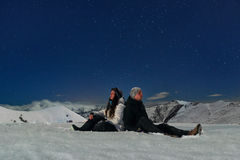 Man and woman sitting on  snow in  mountains Royalty Free Stock Photo