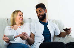 Man and woman sitting on sofa. Black men and white women 25s sitting on sofa with mobiles Royalty Free Stock Photography