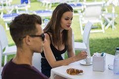 Man and woman sitting at table drinking. Young handsome men and attractive women sitting at white plastic table drinking smoking talking and enjoying themselves Royalty Free Stock Photos