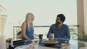 A man and a woman are sitting on the terrace. Man and woman spend time outdoor. Young people are resting on the balcony. Two cups stand on the table. The woman stock video footage