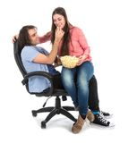 Man and woman sitting together in armchair eating pop corn Royalty Free Stock Photo