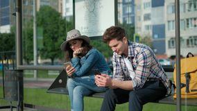 Man and woman are sitting together at transport station. They are holding modern gadgets and entertaining with internet