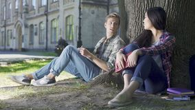 Man and woman sitting under tree, girl saying something, guy looking at her. Stock footage stock footage