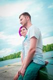 Man and woman sitting on an upturned boat Stock Image