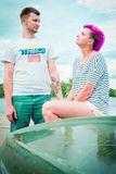 Man and woman sitting on an upturned boat Royalty Free Stock Photography