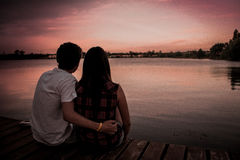 Man and Woman Sitting at Wooden Surface With Man's Hand on Woman's Waist Looking at Sunset Beside a Lake Royalty Free Stock Photos