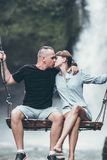 Man And Woman Sitting On Wooden Swing While Kissing stock images