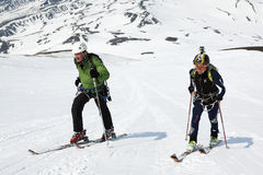 Man and woman ski mountaineer climb on mountain on skis strapped to climbing skins Royalty Free Stock Images