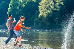 Man and woman skimming stones on river Royalty Free Stock Photo