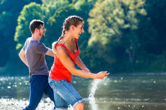 Man and woman skimming stones on river Royalty Free Stock Photography