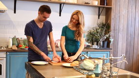 Man and woman slicing bread and ham stock footage
