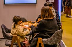 Man, woman and small child sitting at table. Seoul, South Korea, January, 19, 2018: Man, woman and small child sitting at table having a snack at the Seoul Salon Royalty Free Stock Photography