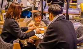Man, woman and small child sitting at table. Seoul, South Korea, January, 19, 2018: Man, woman and small child sitting at table having a snack at the Seoul Salon Royalty Free Stock Images