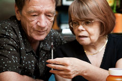 Man and woman with small hypodermic needle Stock Images