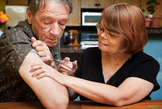 Man and woman with small hypodermic needle Royalty Free Stock Photos