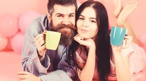 Man and woman on smiling faces lay, pink background. Couple relax in morning with coffee. Couple in love drink coffee in. Man and women on smiling faces lay stock image