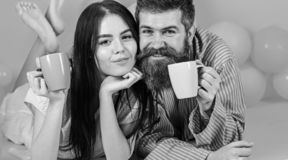 Man and woman on smiling faces lay, pink background. Couple relax in morning with coffee. Couple in love drink coffee in. Man and women on smiling faces lay royalty free stock photography