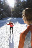 Man and Woman Snow Skiing. Man looking away from camera with woman snow skiing in background.  Vertically framed shot Stock Image