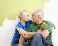 Man and woman snuggling while painting. Royalty Free Stock Image