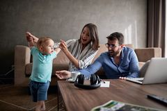 Man and woman spending happy time at home with their baby son an. Young men and women spending happy time at home with their baby son and playing together royalty free stock images