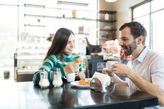 Man And Woman Spending Time In Cafe. Loving couple having coffee and chouxs while enjoying date in bakery royalty free stock image