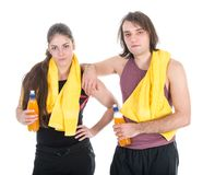 Man and woman in sports wear relaxing with orange juice, isolated over white Royalty Free Stock Photos