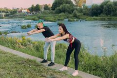 A man and a woman in sportswear doing stretching on the river bank.