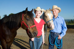 Man and Woman Stand With Horses - horizontal Royalty Free Stock Images